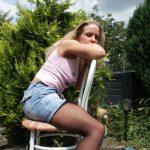 Blondine in Strumpfhosen sitzt auf Stuhl im Garten